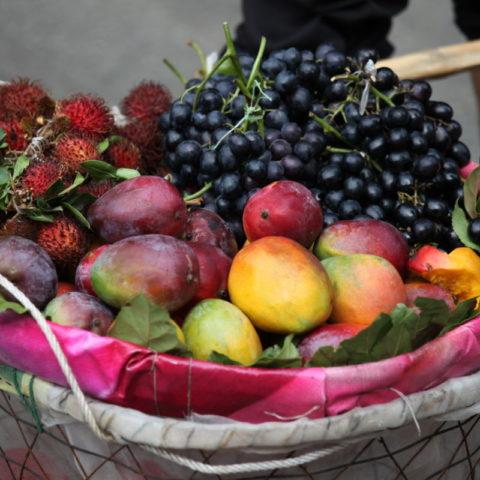 Uliczny sprzedawca owoców w Chinach. W koszyku ma rambutany, mango, śliwki i winogrona